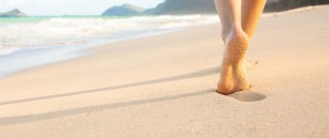 Bare feet and lower legs walking along the sand on a beautiful beach