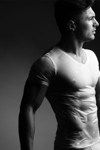 Athletic younng man in wet white t-shirt showing good body definition. Face in profile.