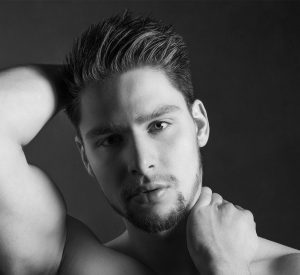 Young man's face with a soulful expression and even skin tone, soft lighting and plain background.