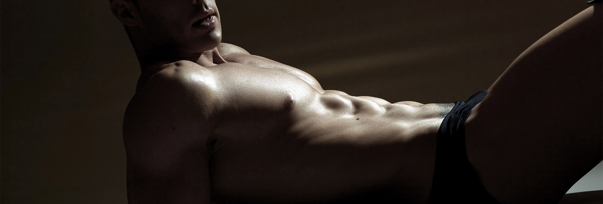 Athletic naked hair free male torso with rippling abdominals side on lying pose.