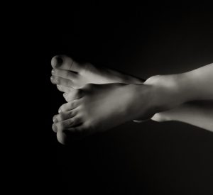 immaculate feet crossed in subtle lighting with dark background.