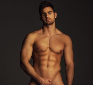Muscular young man's naked torso and face in a provactive pose.