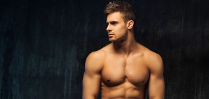 Handsome young man's face in profile and naked upper muscular torso on plain bacground.
