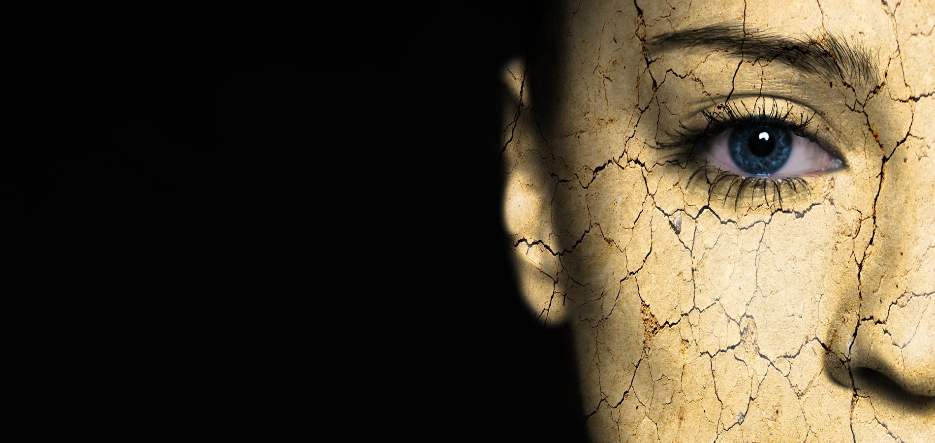 Woman's half face with superimposed cracked earth on skin to give the effect of very rough skin needing exfoliation.