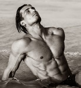 Handsome young athletic man with naked defined torso, relaxing at the beach in the water.