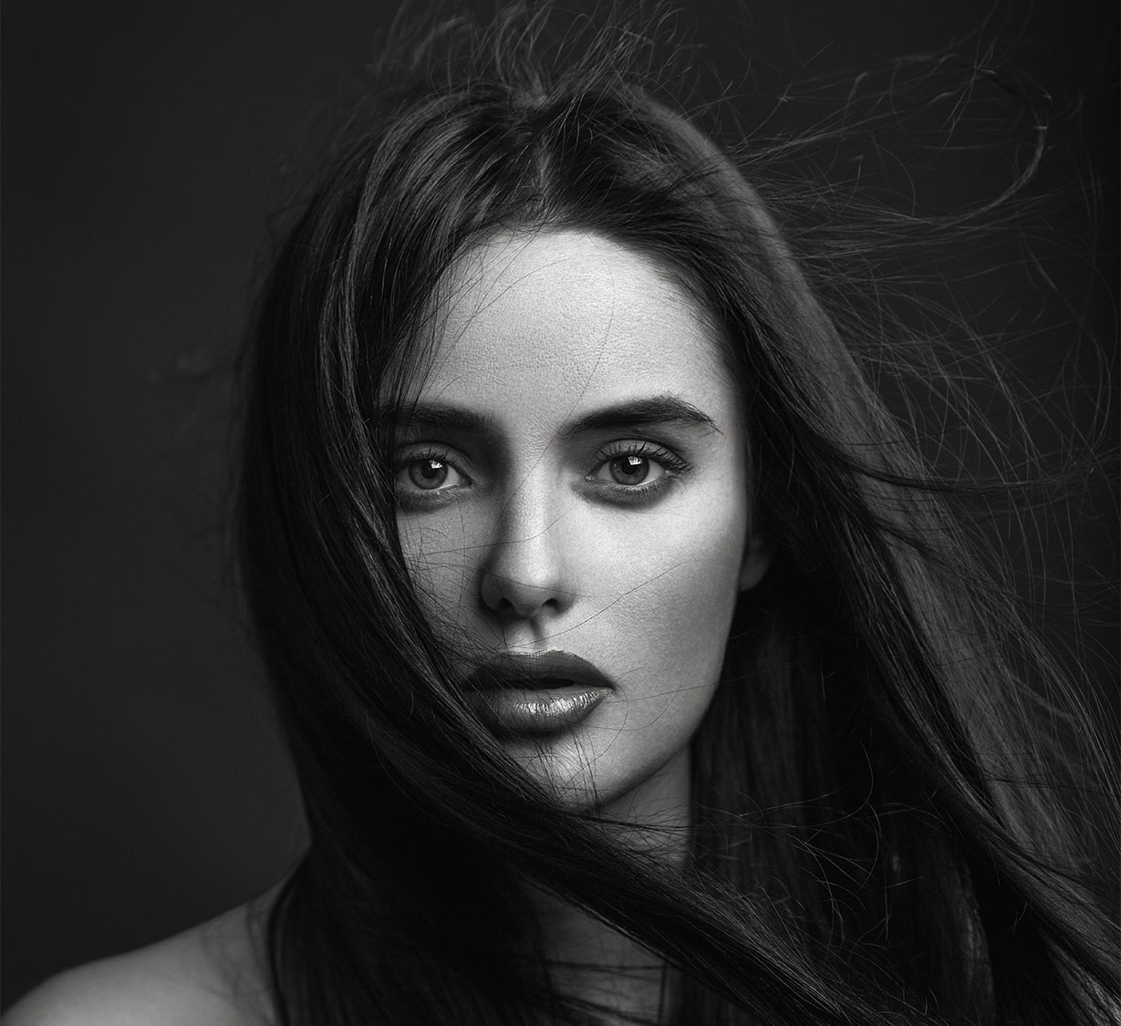 Sultry young woman's face and even skin tone with windswept hair black & white image