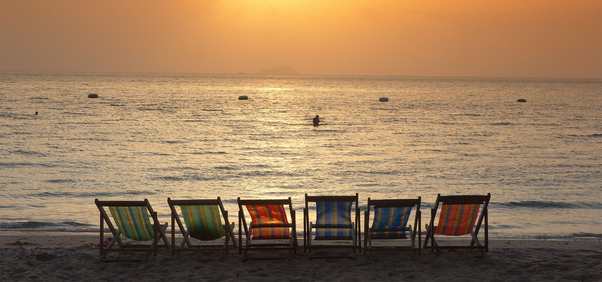 Empty deck chairs on the sand at the beach with the sun setting in the background.