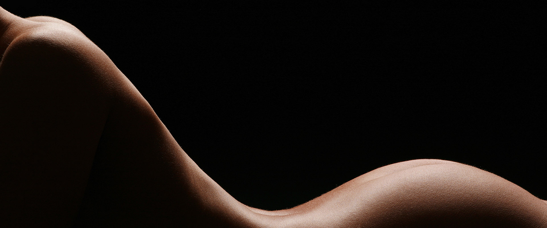 Silhouette of womans tanned naked torso and buttocks on black background.