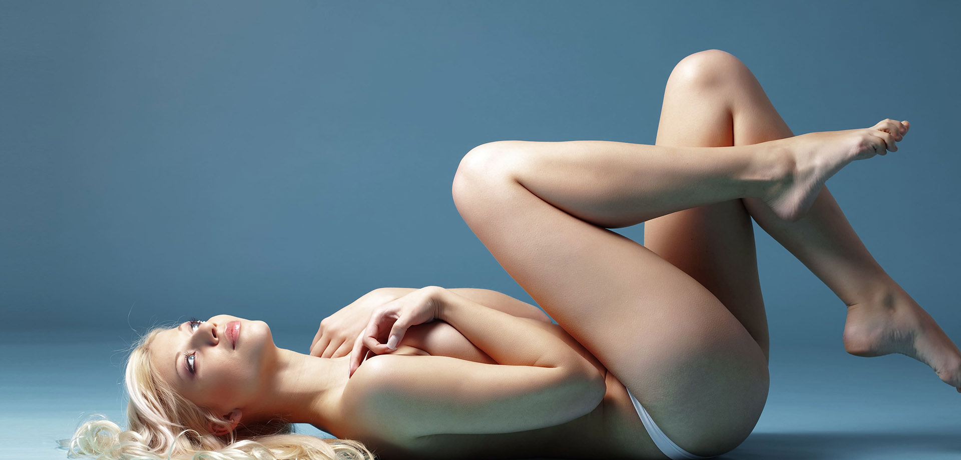 naked Young woman covering her breasts in a lying pose with long blond hair and hair free body.