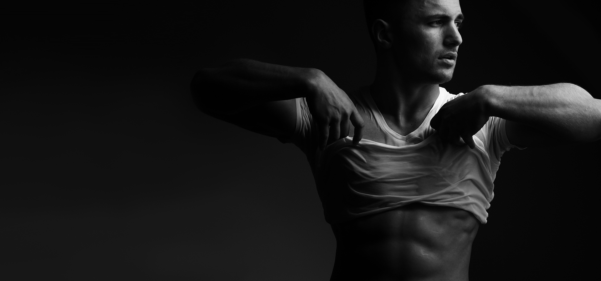 male lifting his t-shirt to show defined abdominals