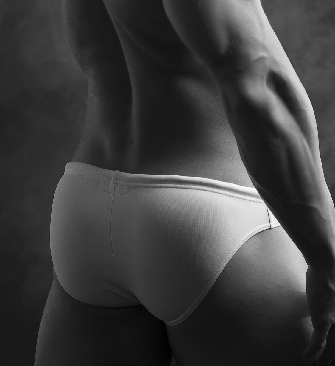 Young mans muscular buttocks in white speedos