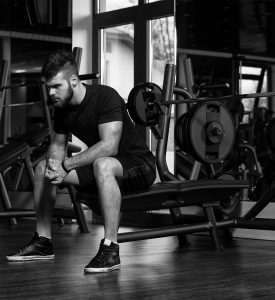 Young man sitting on a workout bench in a gym in deep thought