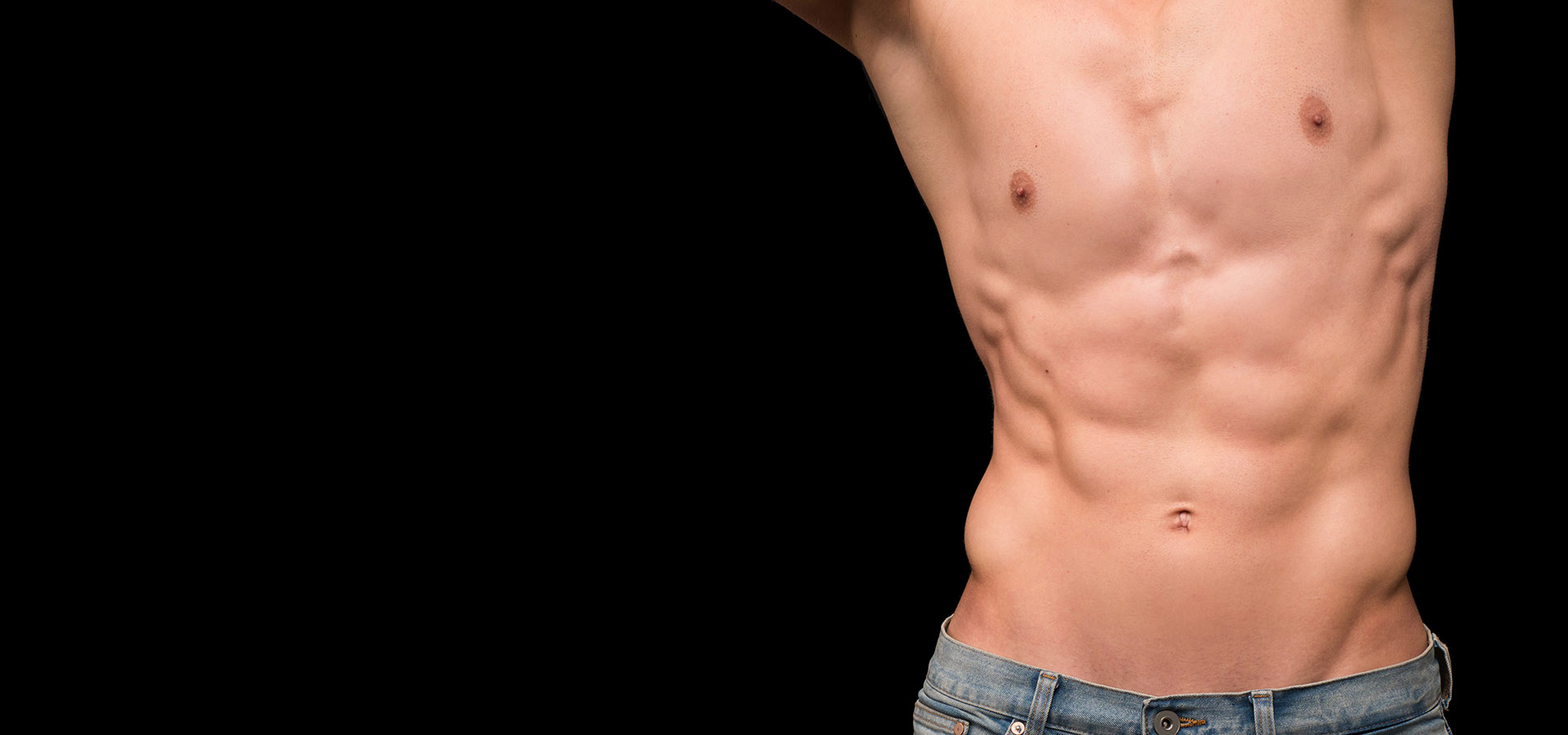 Young mans torso with arms above head showing defined abdominals