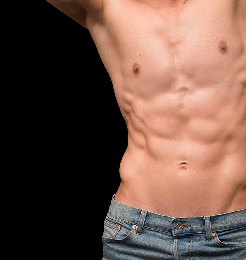 Young mans bare torso with arms up showing defined abdominal muscles